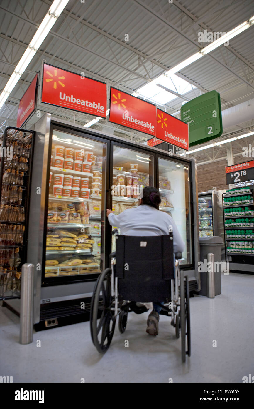 Man in a wheel chair reaching trying to open freezer
