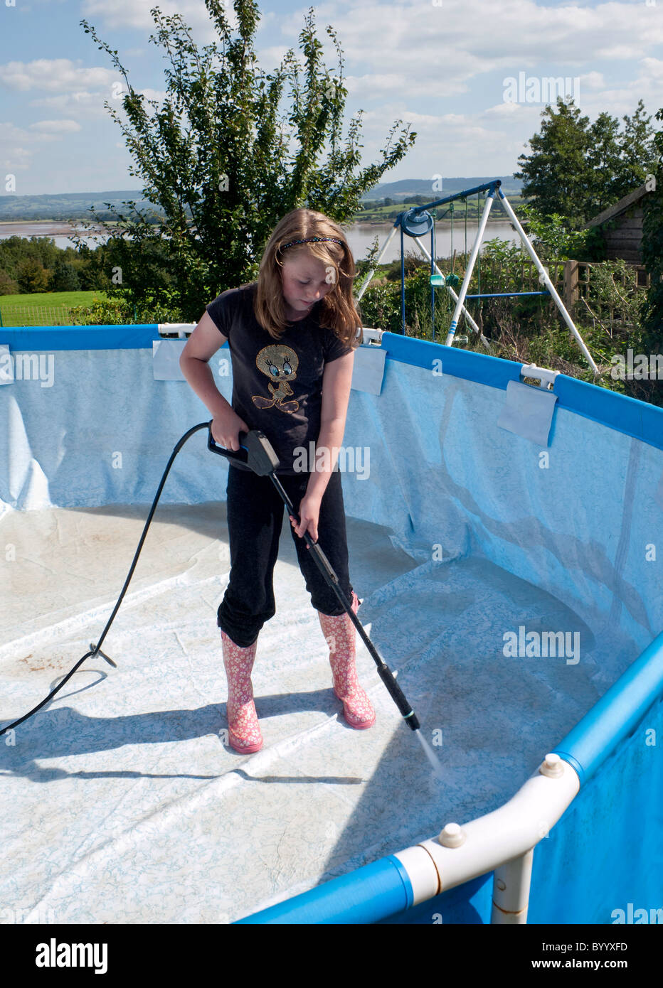 Young girl cleaning empty collapsible swimming pool in for Garden pool uk