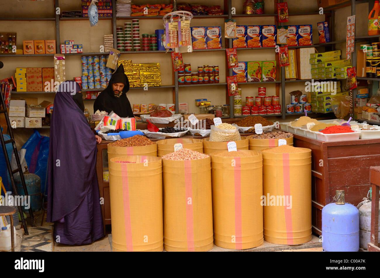 grocery store worker in djellaba female customer in purple grocery store worker in djellaba female customer in purple hijab in fes el bali medina fez north africa
