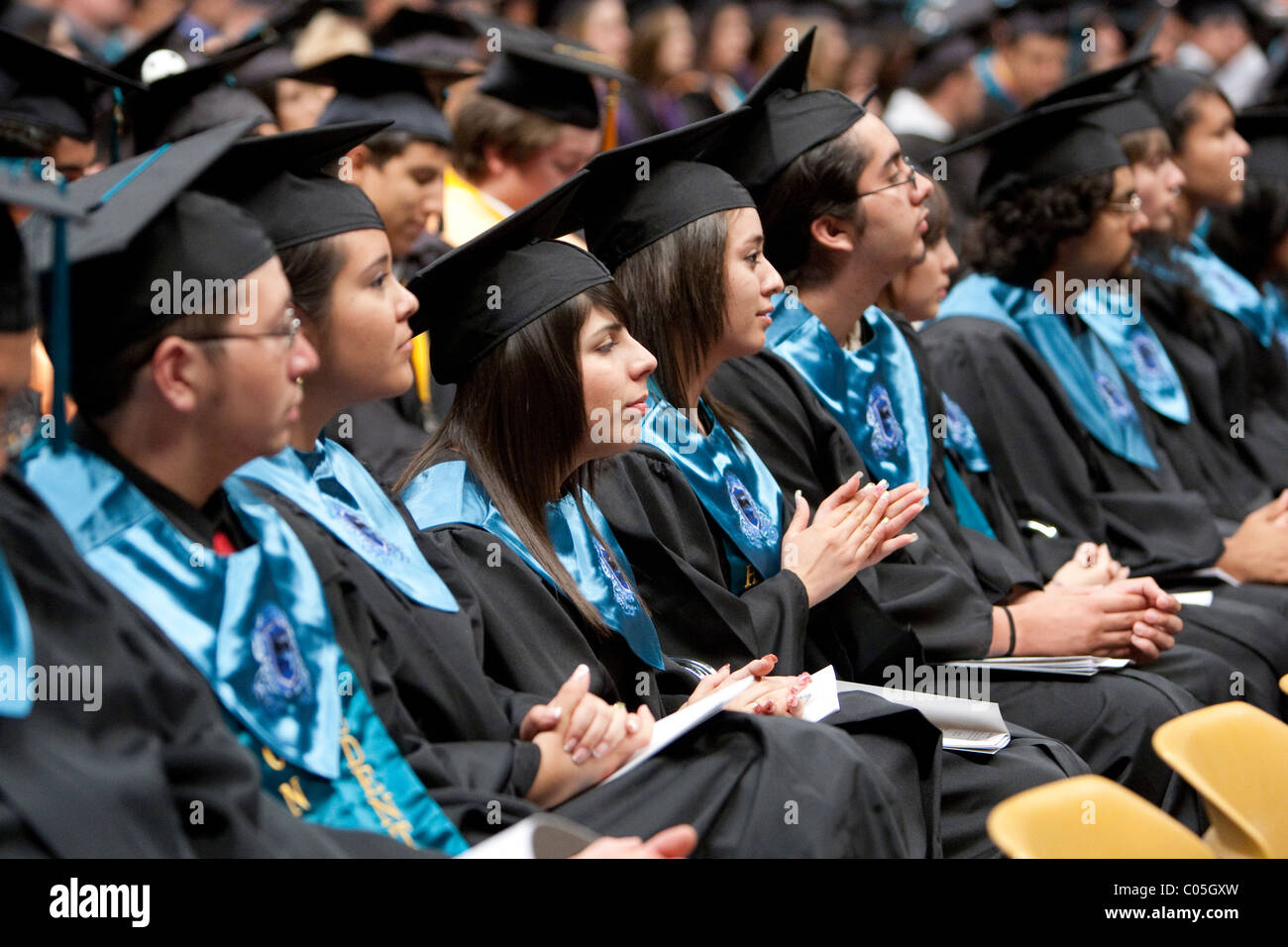 High school seniors in caps and gowns sitting in a row wait to ...