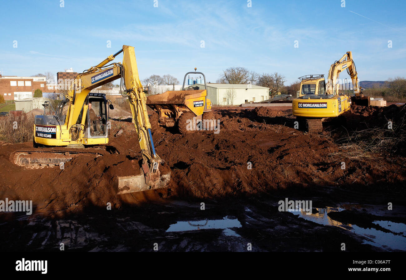Mechanical diggers excavating earth on a building site for Images of building sites