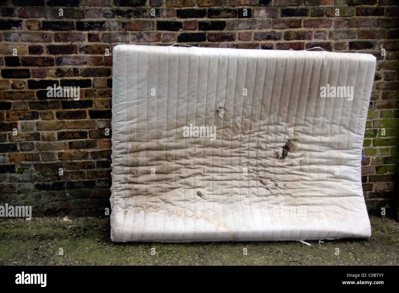 Dirty old mattress left on a street in London Stock