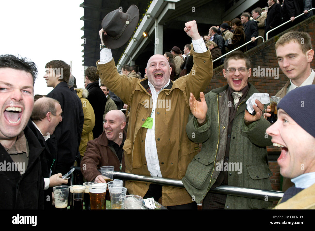 a group of men jumping for joy after watching the horse they bet a group of men jumping for joy after watching the horse they bet on win at cheltenham races