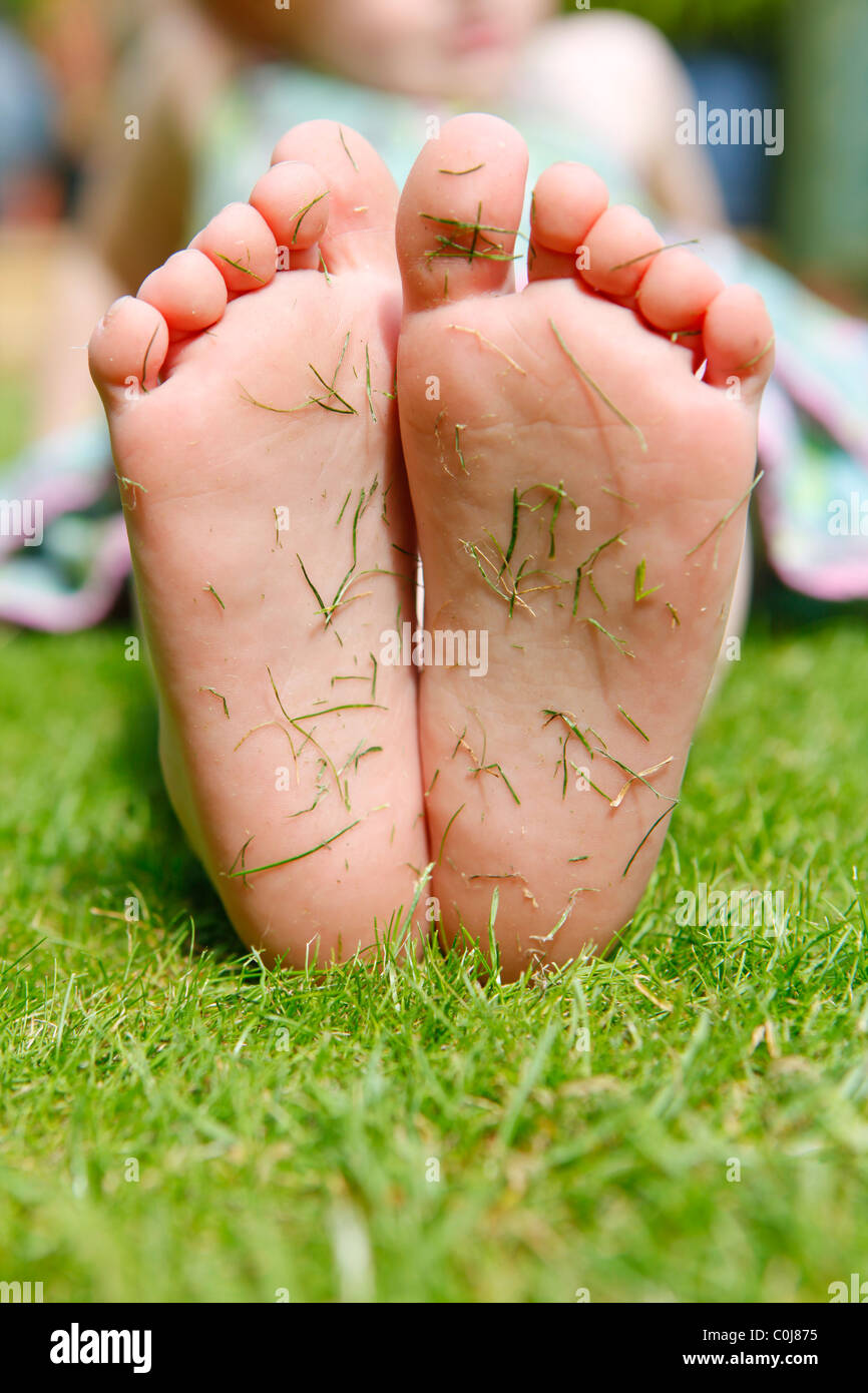 girlfeet Little girl feet covered in grass cuttings in the garden in the summer time.
