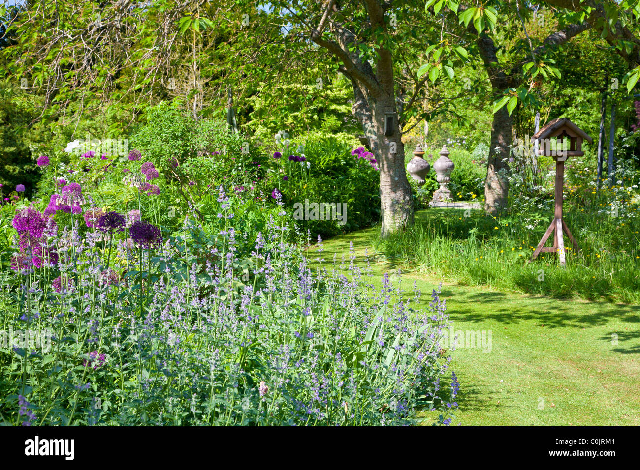 A Corner Of An English Country Garden With A Grassy Path