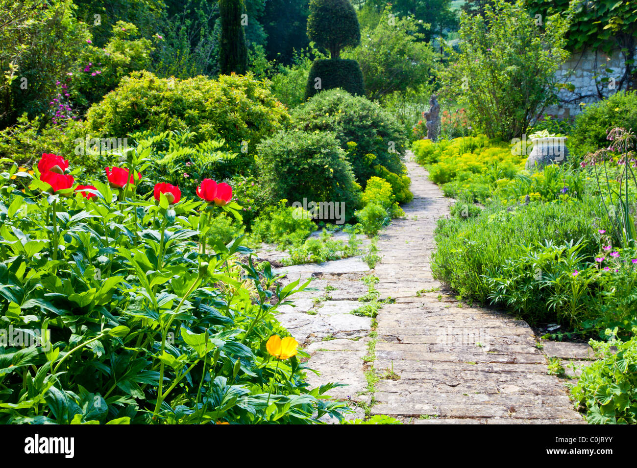 a paved garden path between shrub and flower borders in an english country garden in summer - Flower Garden Path