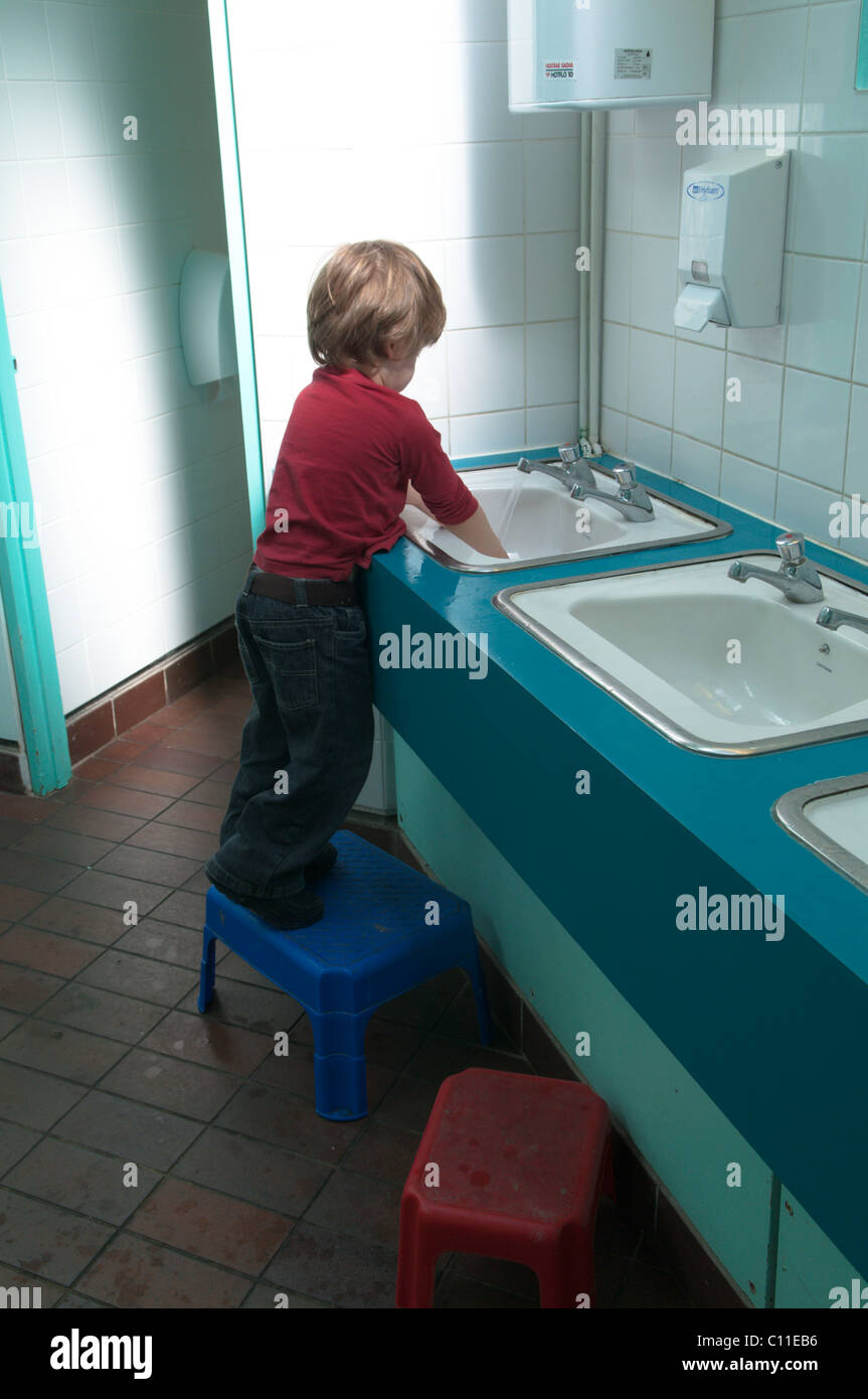 Stock Photo   three years old boy in public restroom cloakroom toilets  standing on a stool to wash hands after using toilet. three years old boy in public restroom cloakroom toilets standing