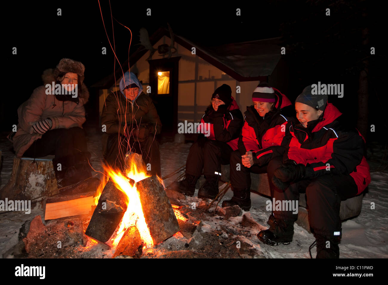 People Sitting At A Camp Fire Illuminated Wall Tent