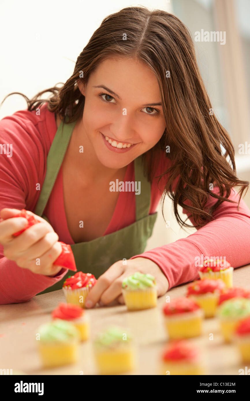 usa utah lehi portrait of young woman decorating cupcakes in kitchen - Woman Decorating Cupcakes