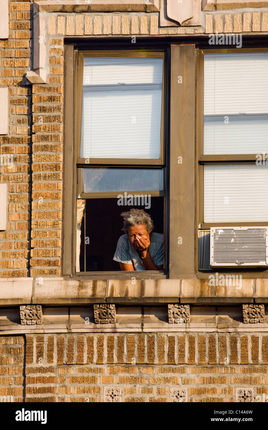African American Woman Looking Out Apartment Window In New