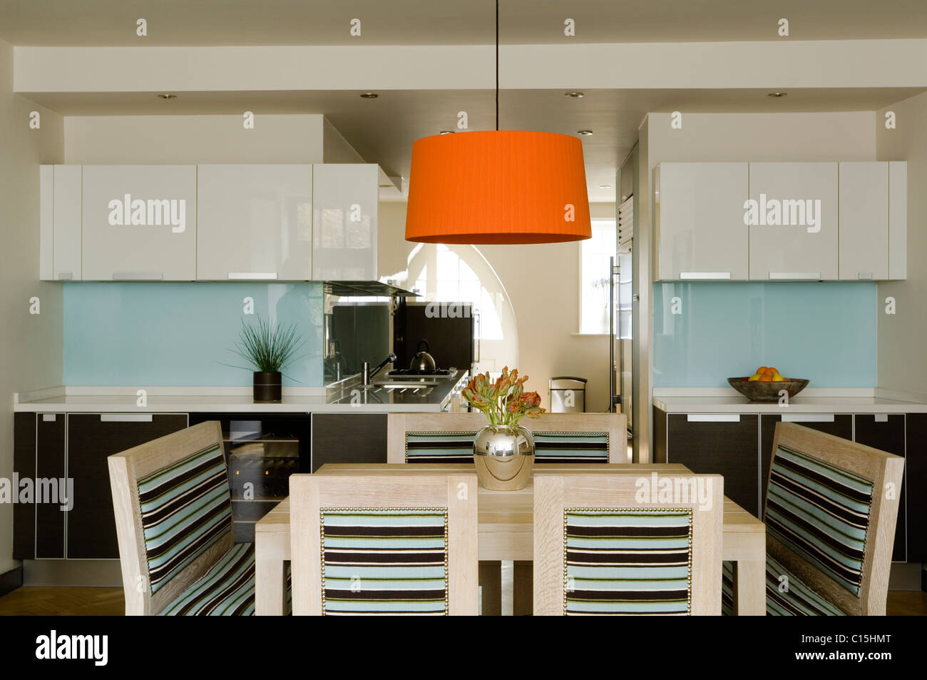 Large orange lampshade above dining table in open plan kitchen