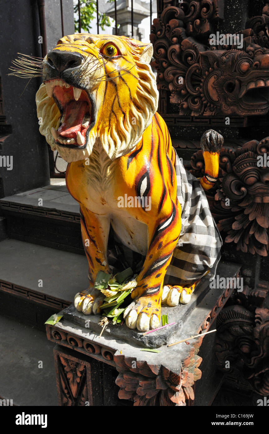 statue of a tiger made of stone in front of the temple gate in