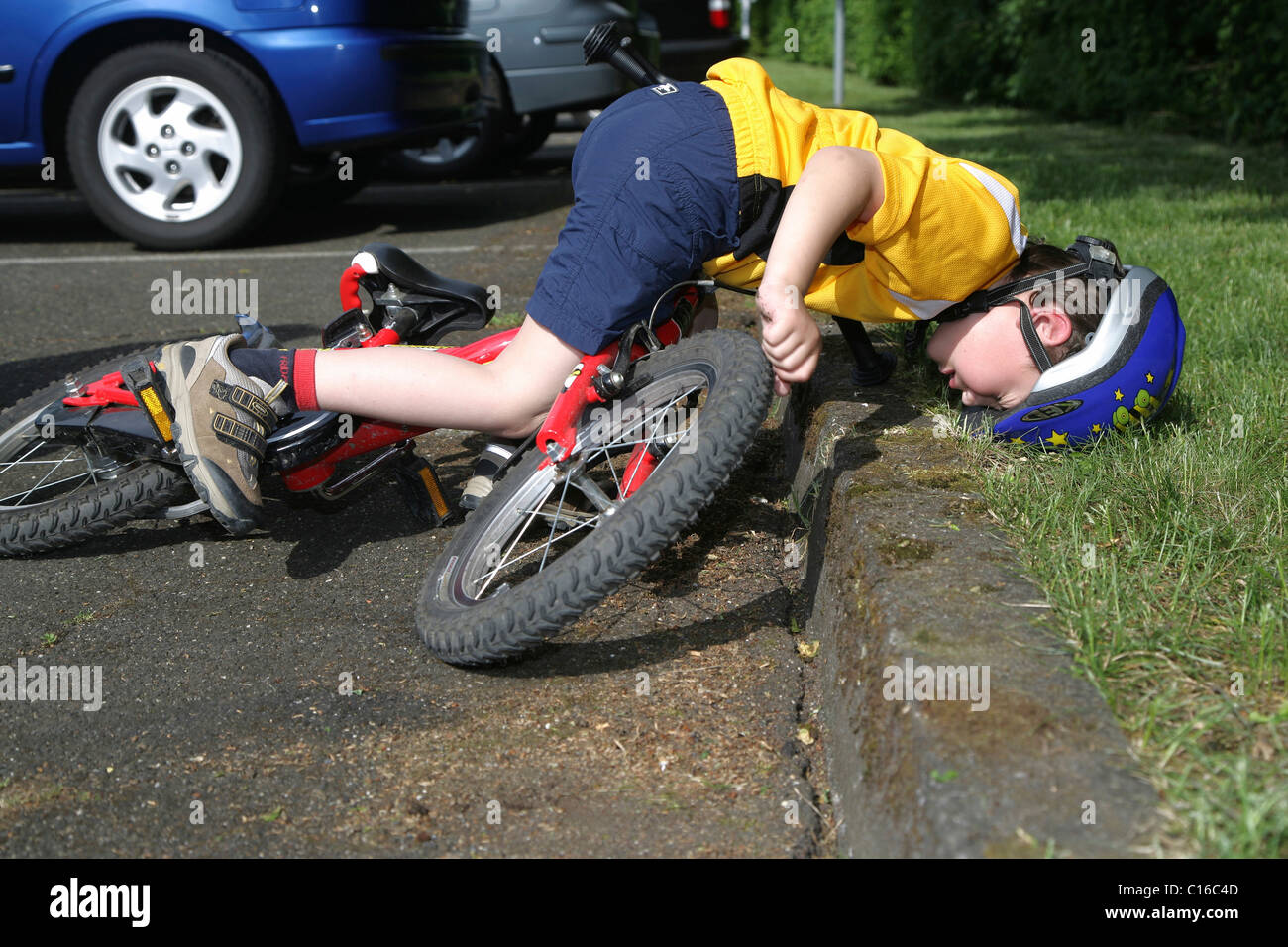 Five-year-old boy wearing a bicycle helmet falling off his ...