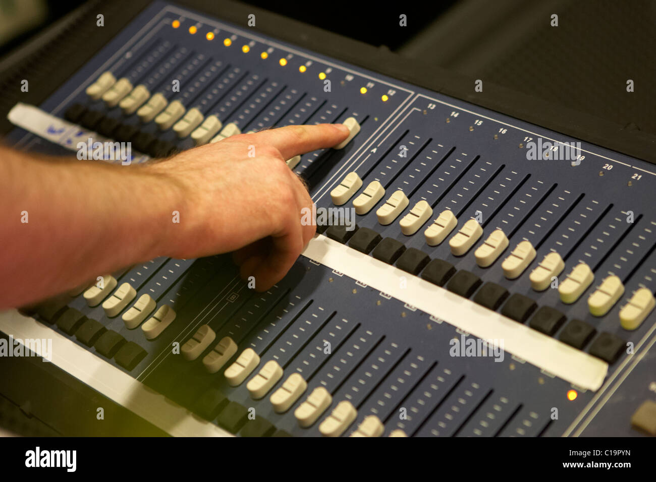 lighting engineer adjusting sliders on a lighting mixing desk in a theatre concert hall & lighting engineer adjusting sliders on a lighting mixing desk in a ... azcodes.com