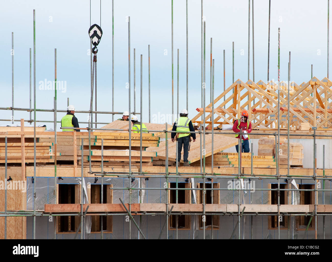 Building contractors at work on housing on a construction for Housing construction companies