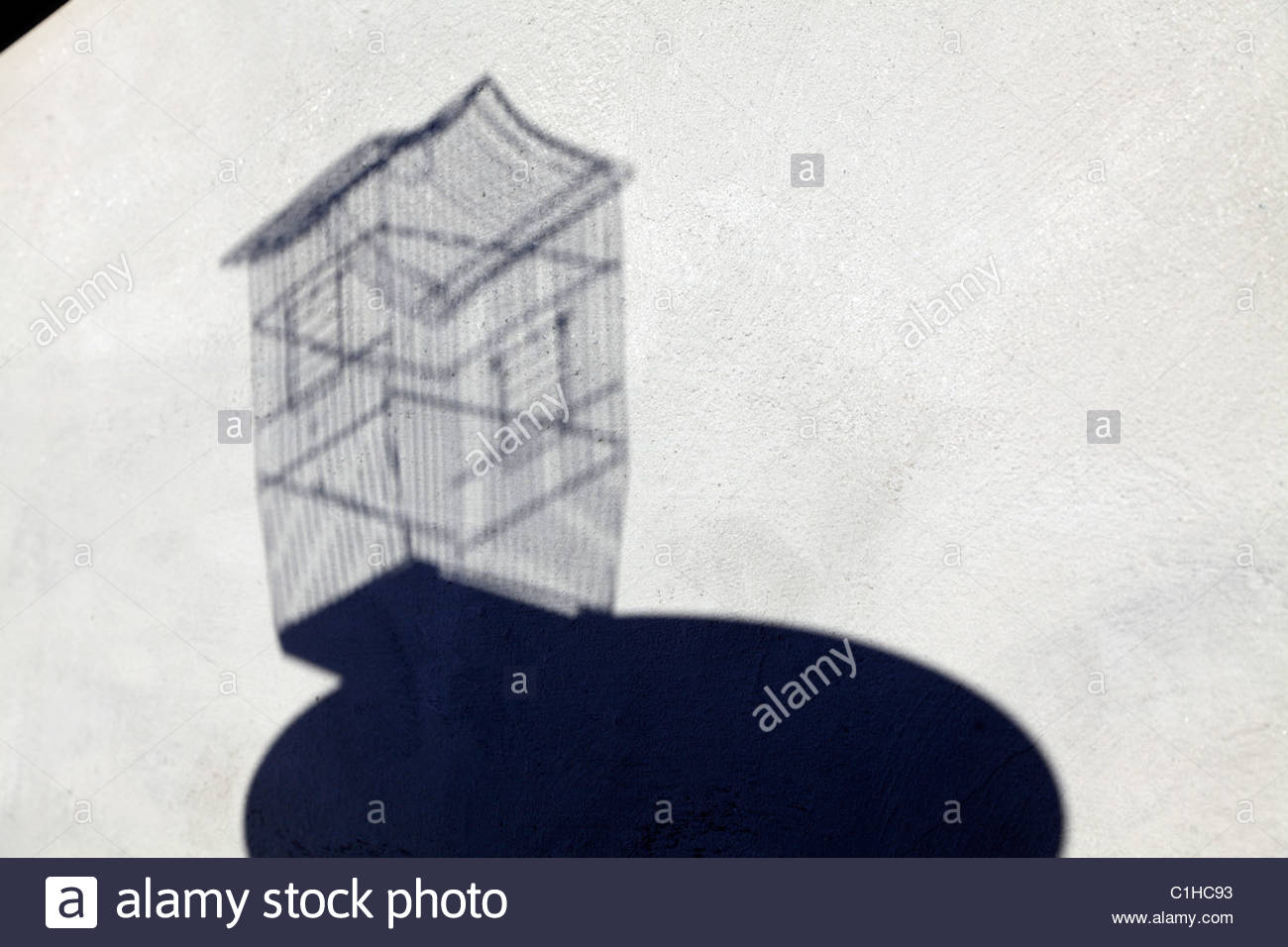 Stock Photo   Shadow Of Empty Birdcage On A Little Round Table