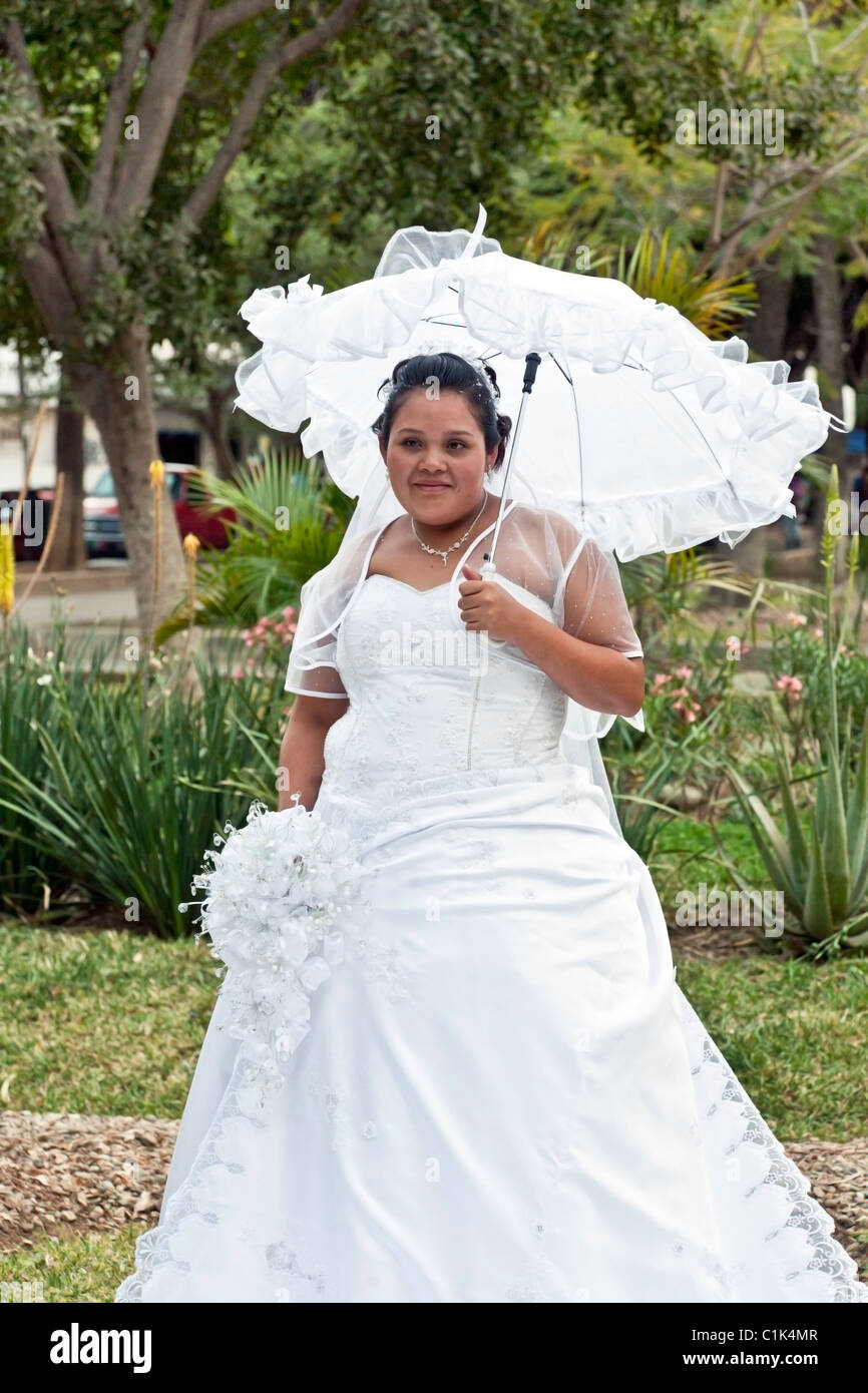 Plump smiling bride poses in her wedding dress under shade for Best wedding dresses for short fat brides