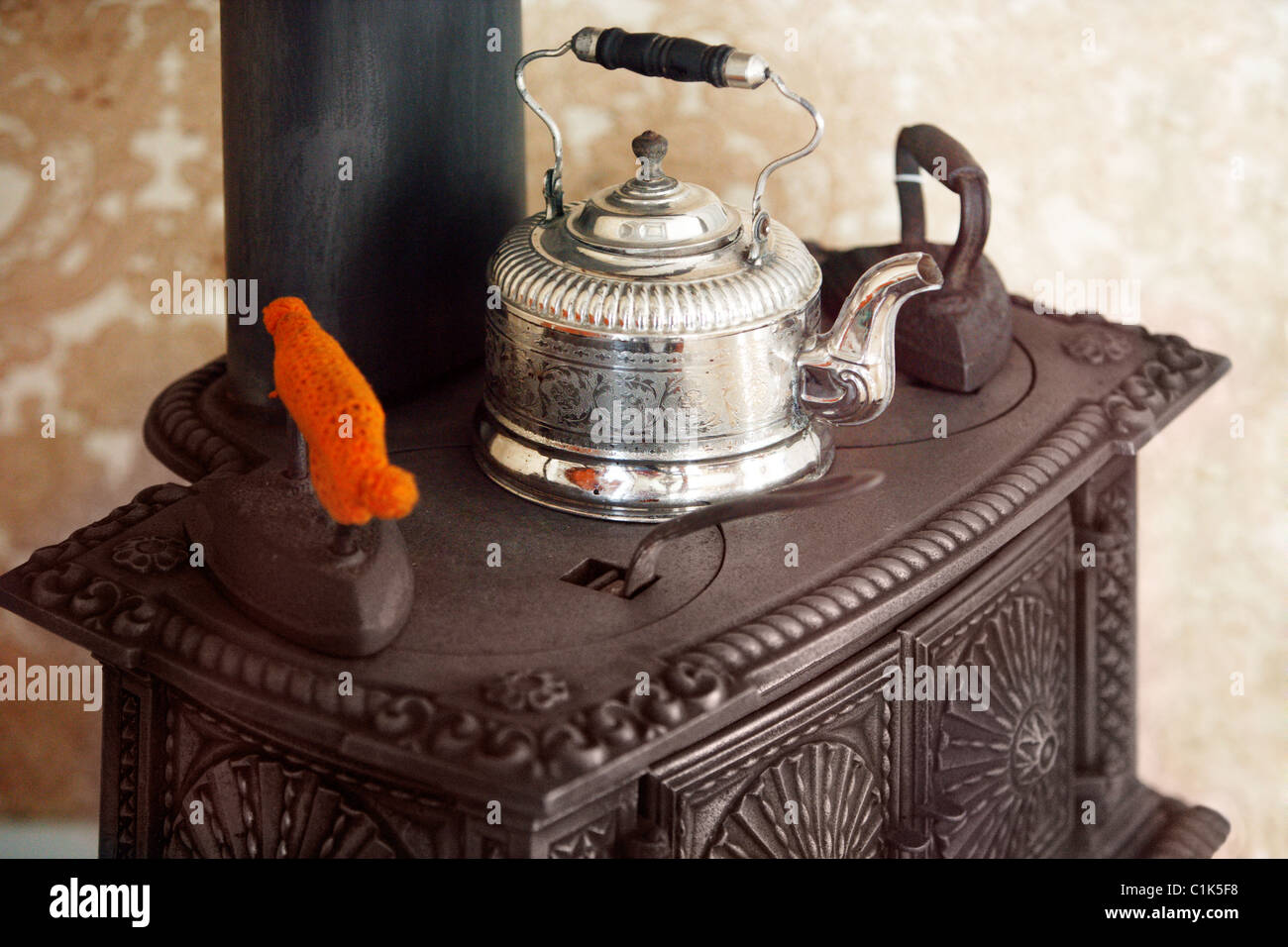 An Antique Cast Iron Stove With A Teapot And Antique Irons