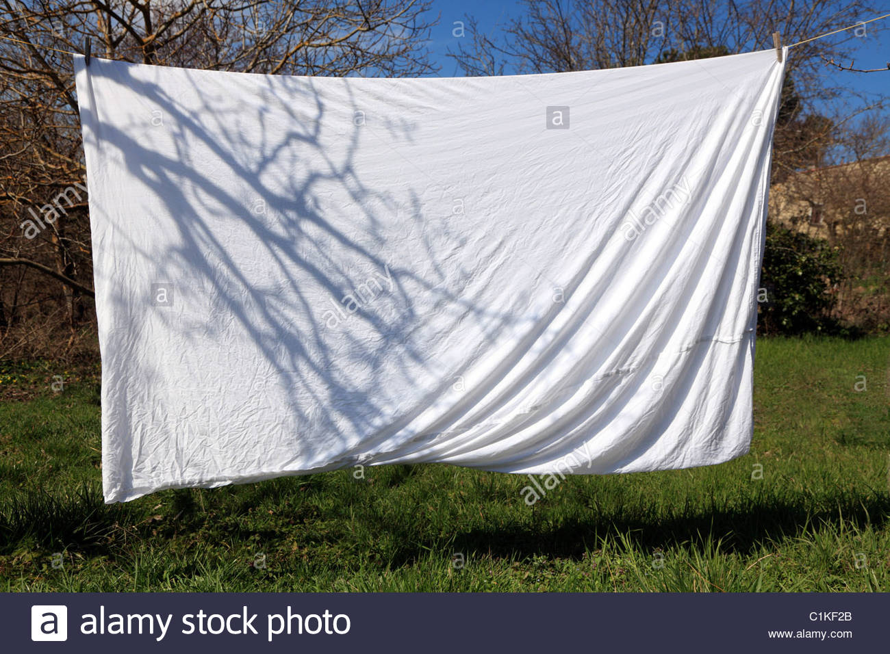 Bed sheet drying outside on washing line stock photo for Como blanquear cortinas