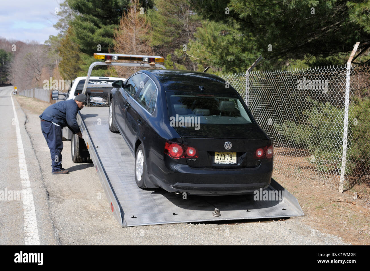 Broken down car being loaded onto a flatbed wrecker truck