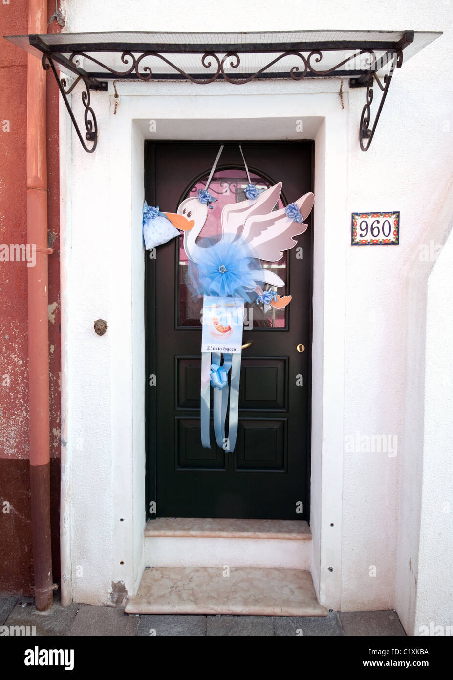 A stork sign hanging outside a house door announcing the birth of – Announcing a Birth