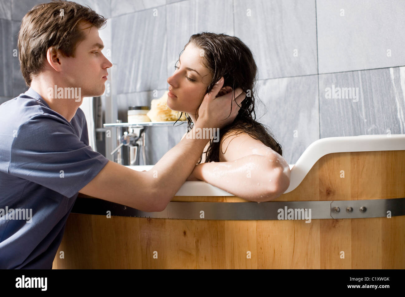 Man kissing woman in bathroom   Stock Photo. Couple kissing in the bath Stock Photo  Royalty Free Image