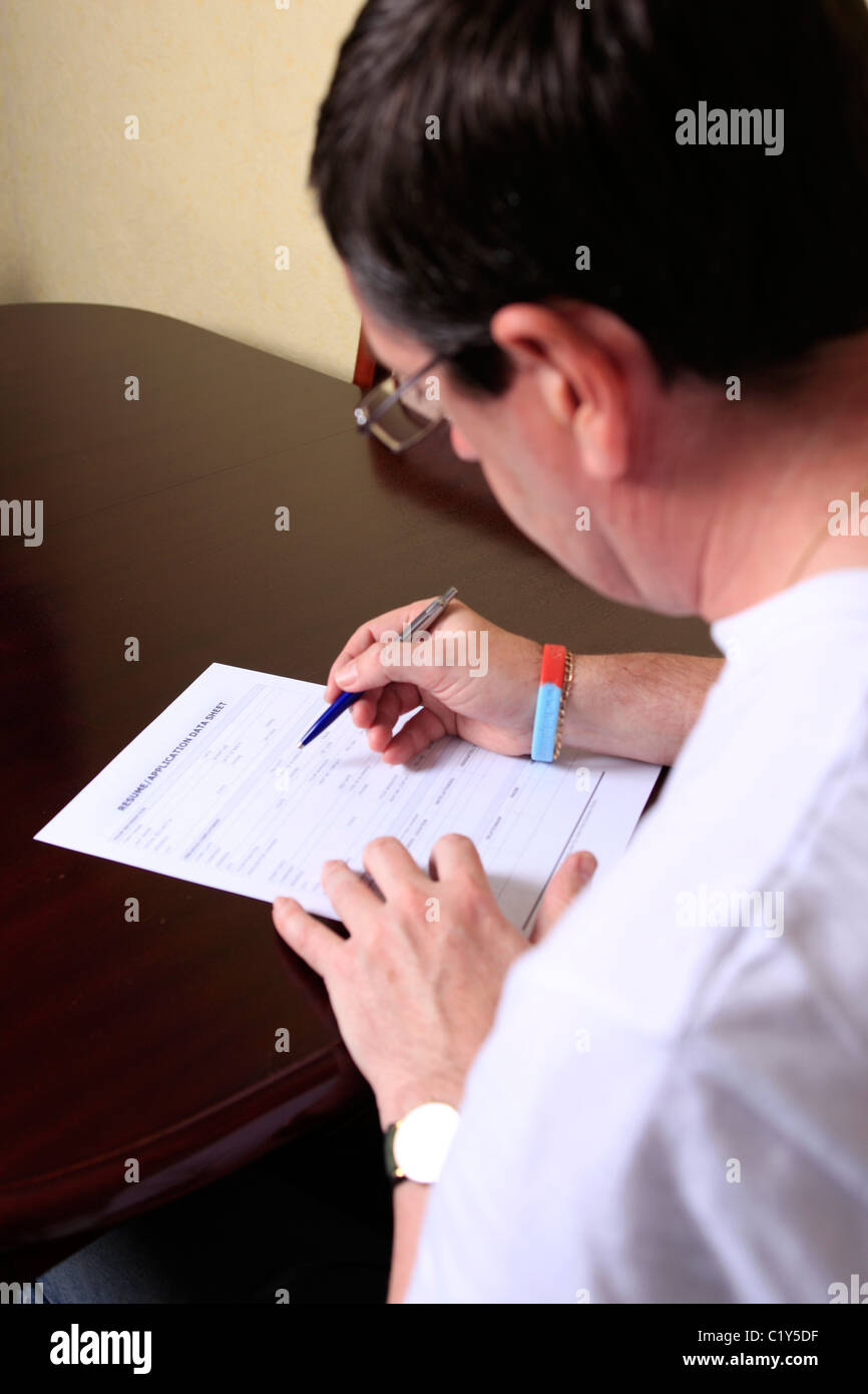 adult man sitting at home filling out a job application form stock adult man sitting at home filling out a job application form