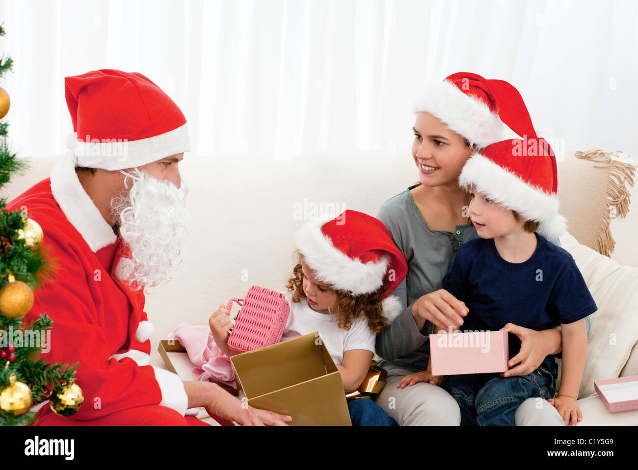 Santa Giving Presents To His Children In The Living Room Stock Photo Royalty Free Image