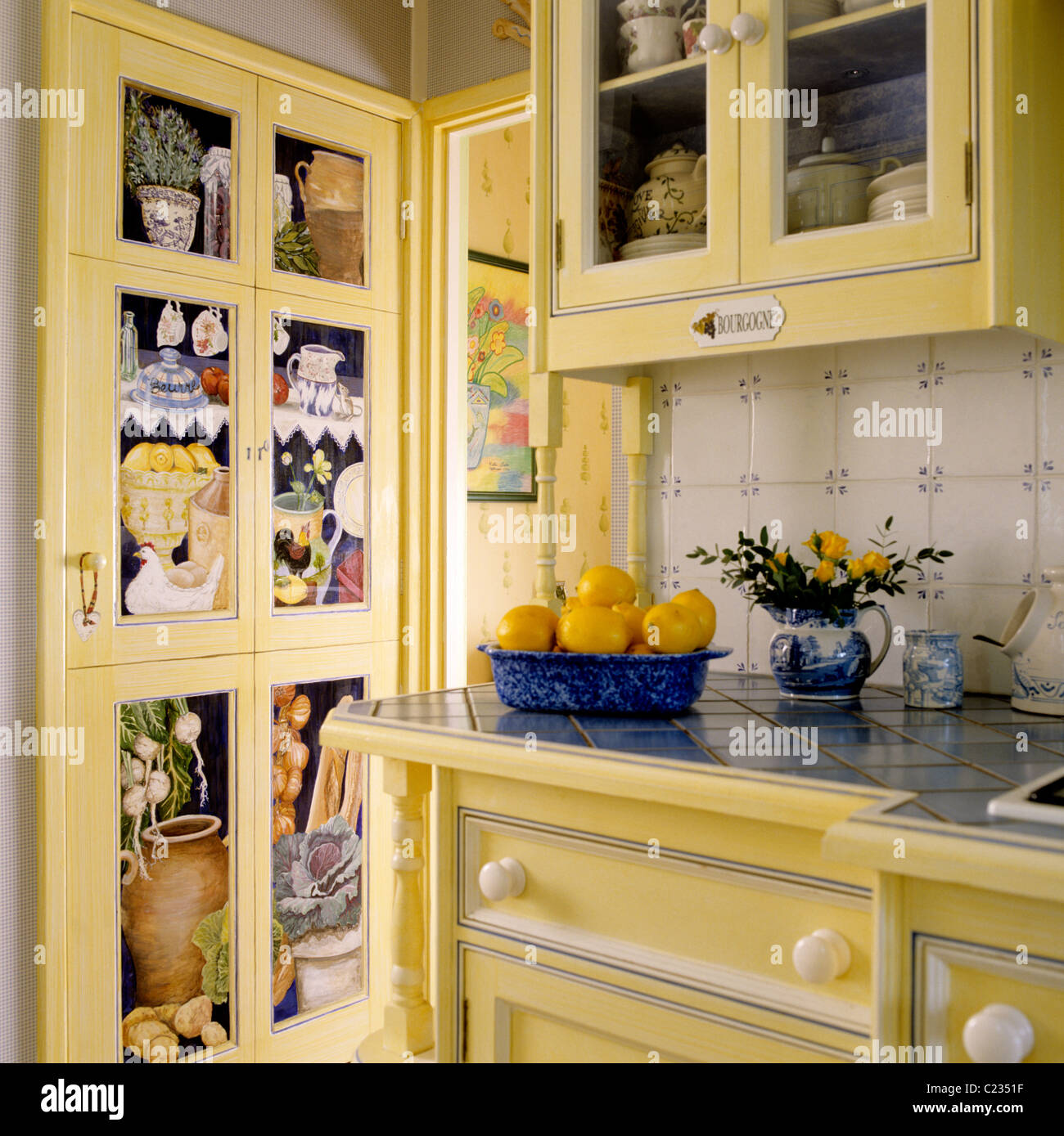 Lemons In A Traditional English Style Kitchen With Yellow Painted Cupboards  And Drawers