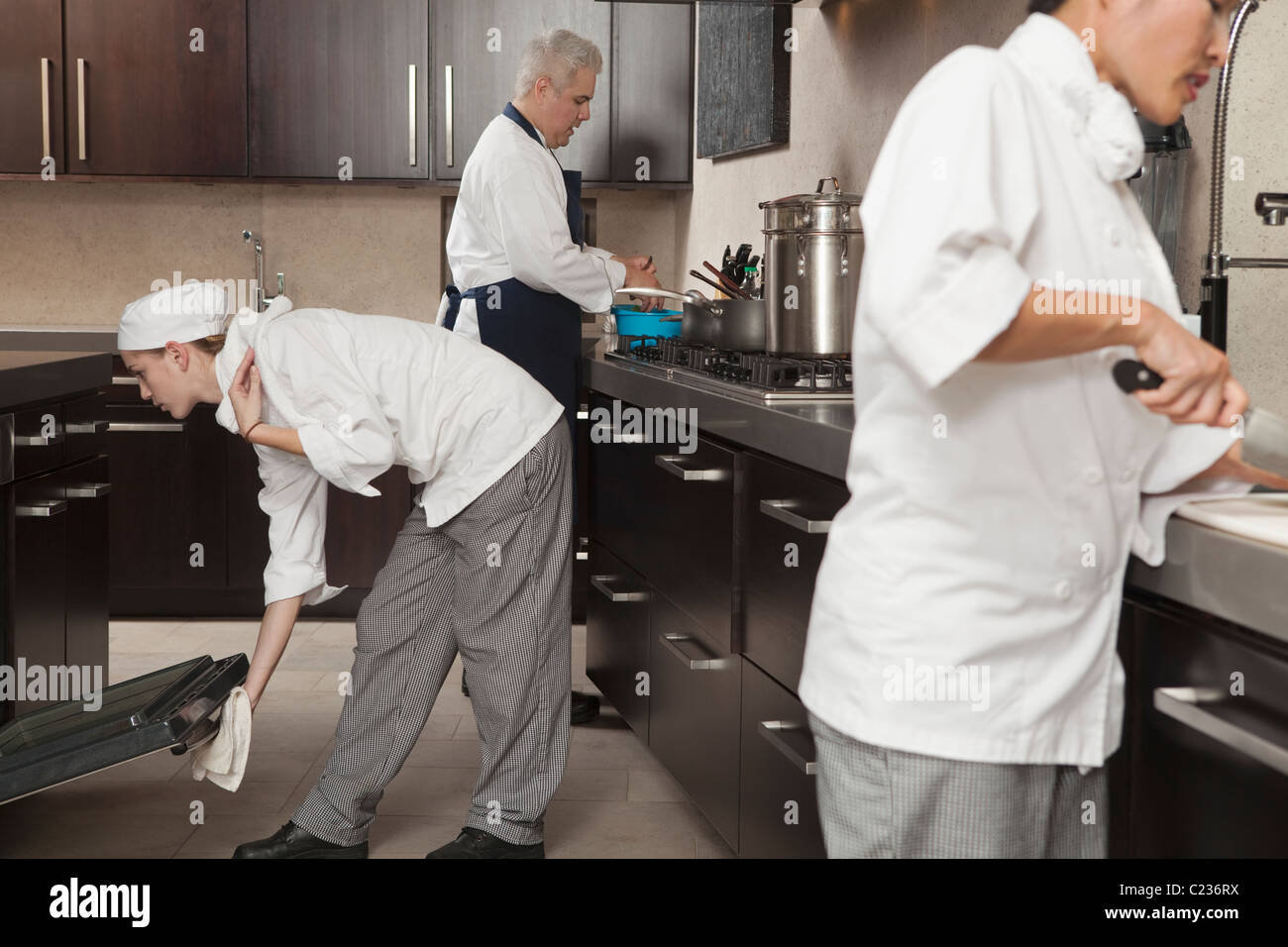 Busy Kitchen three chefs work together in busy kitchen stock photo, royalty