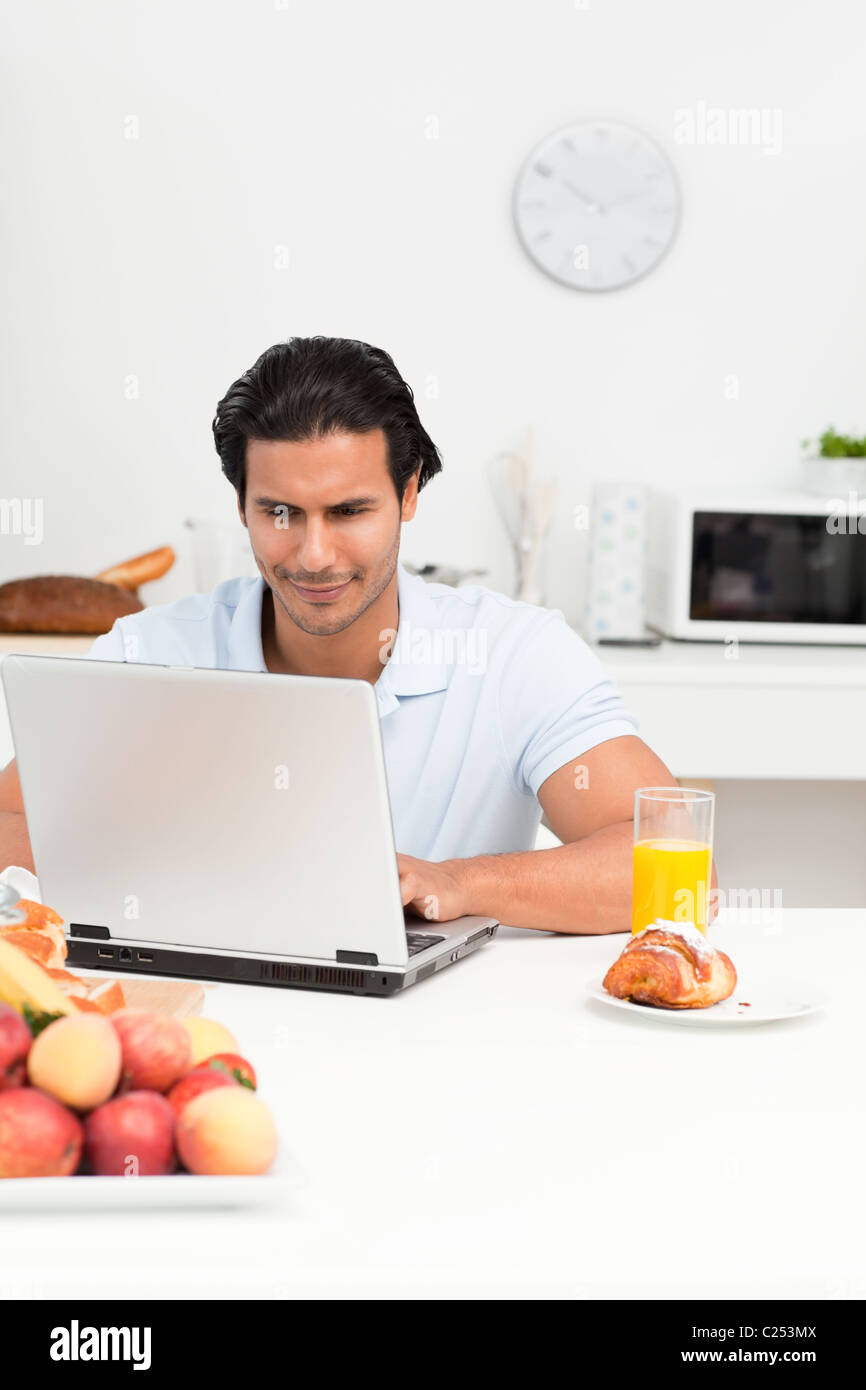 Charismatic hispanic man working on his laptop in the kitchen Stock ...