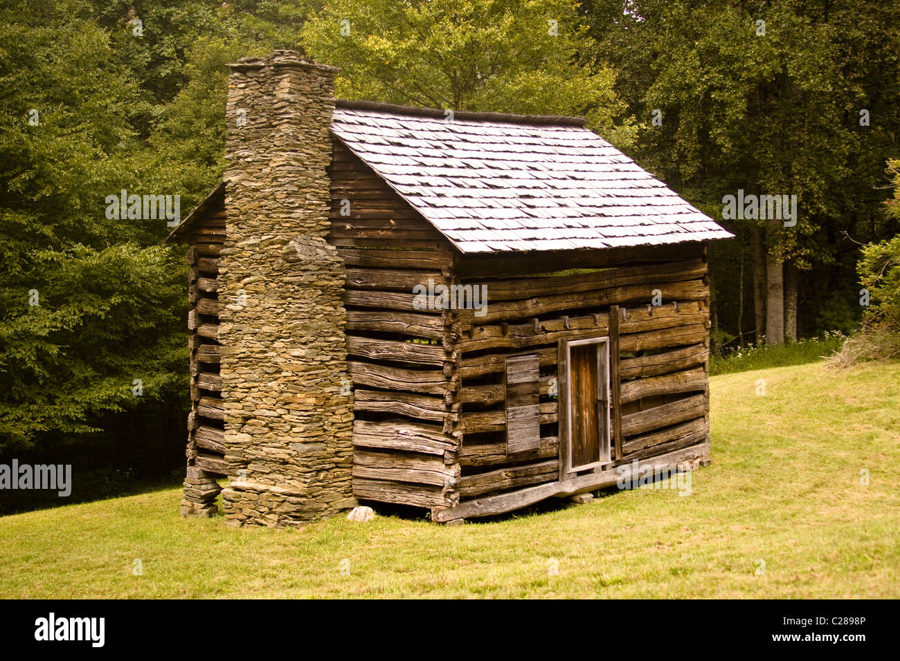 A log cabin with stone chimney in a grassy field for Stone chimneys