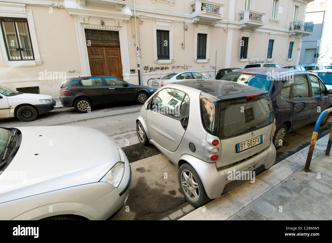 smart car cars small tiny parked end on to kerb in city cities