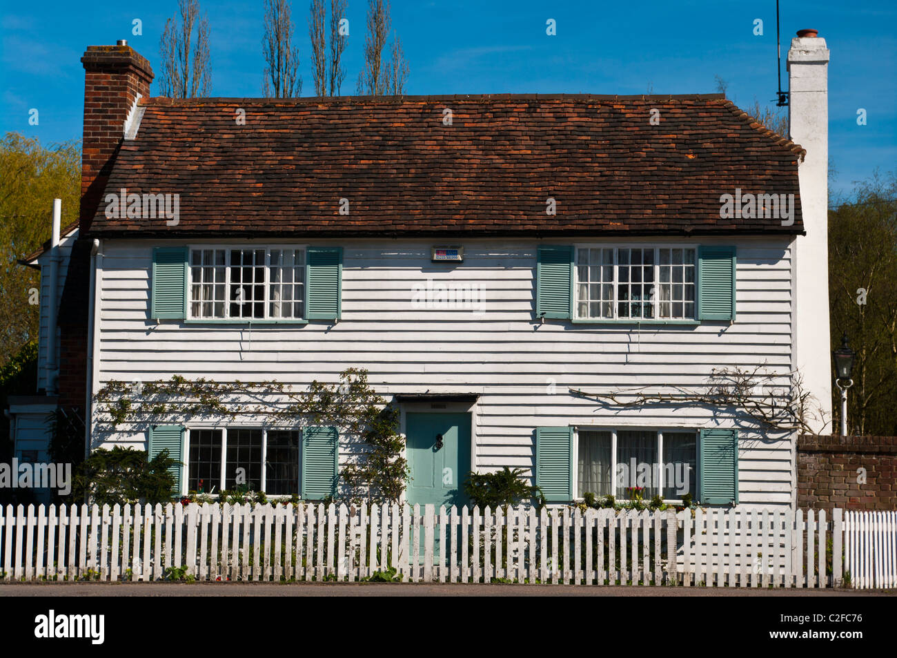 White country cottage with blue window shutters and a for Country shutters