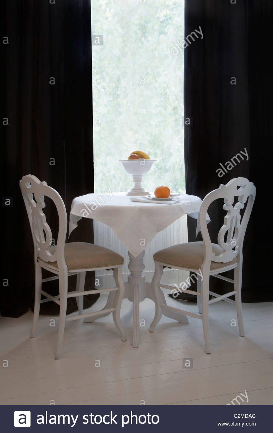 Small Round White Table With Fruitbowl And Two Chairs In