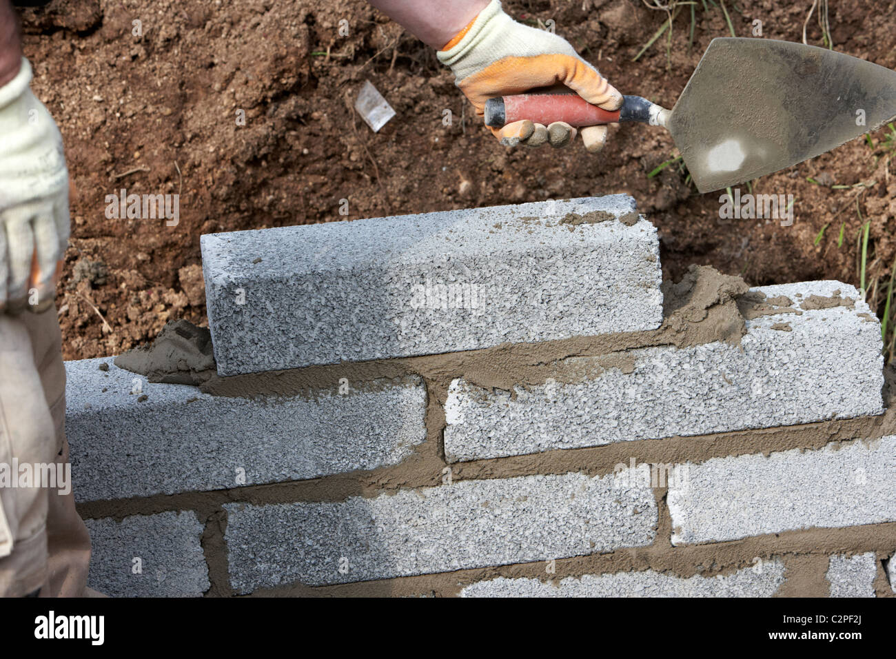 Bricklayer with trowel building a wall with half cement for Building a concrete block house