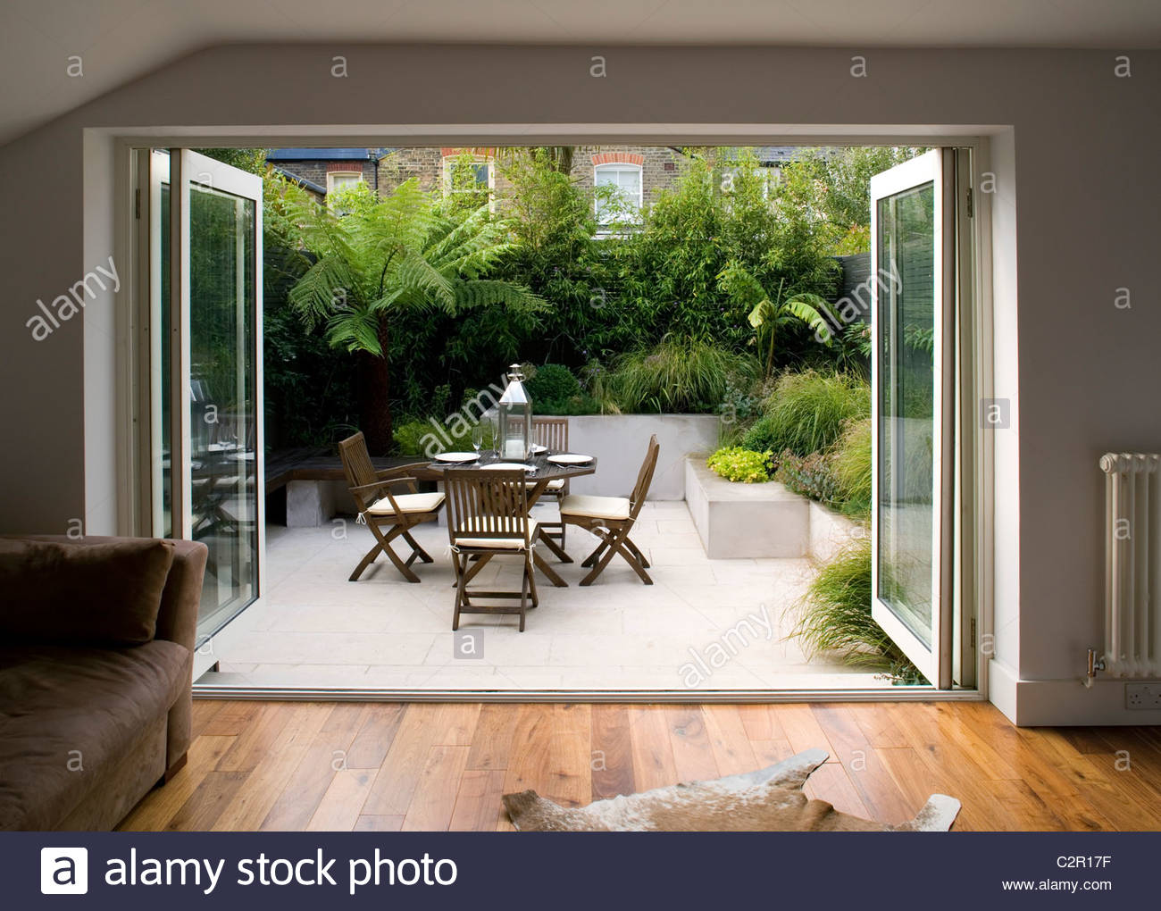 Living room with bi fold doors opening on to patio with for Patio furniture for narrow balcony