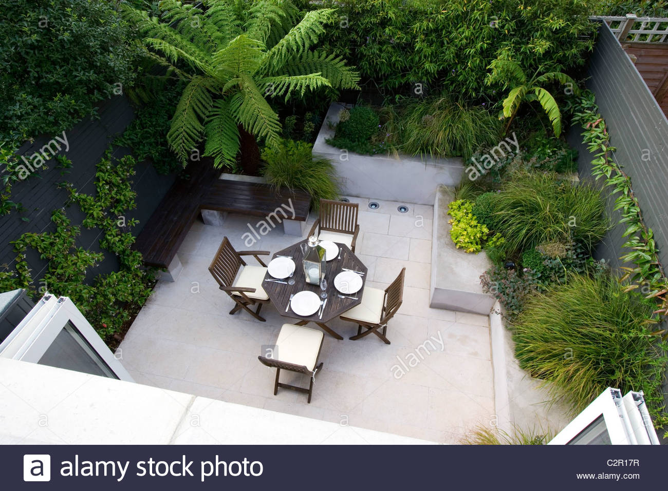 Small Town Garden With Patio With Raised Beds, Tree Fern And Table And  Chairs