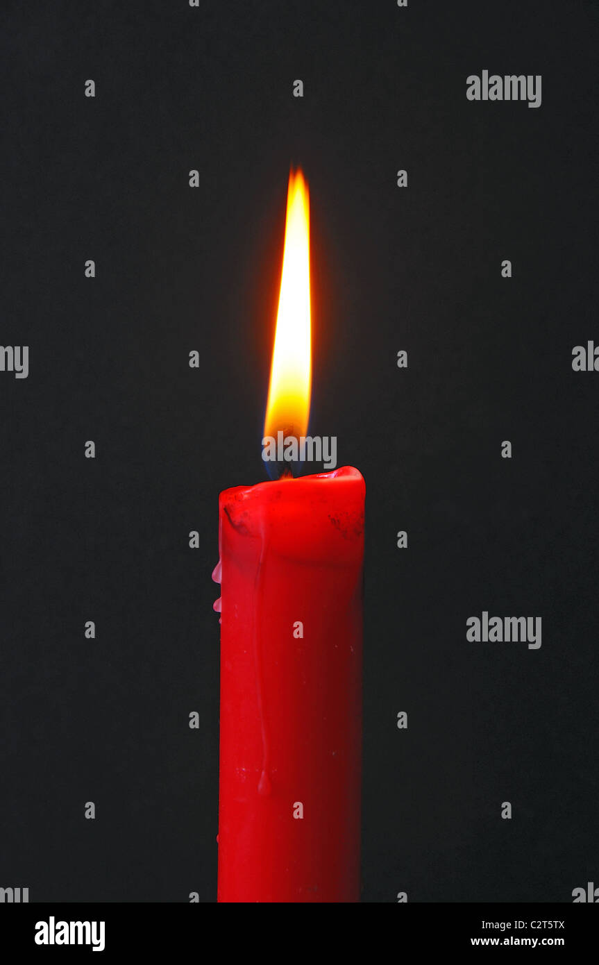 Red candle against a black background Stock Photo, Royalty ...