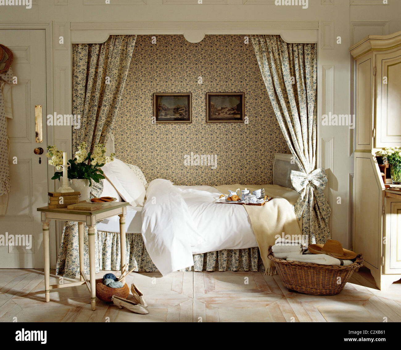 double bed set in recess with patterned curtains and wallpaper