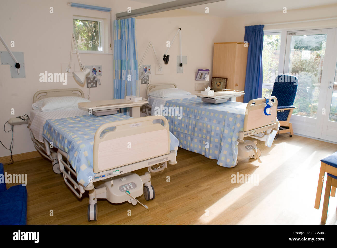 two hospital beds in a hospice with the sun shining in and big windows