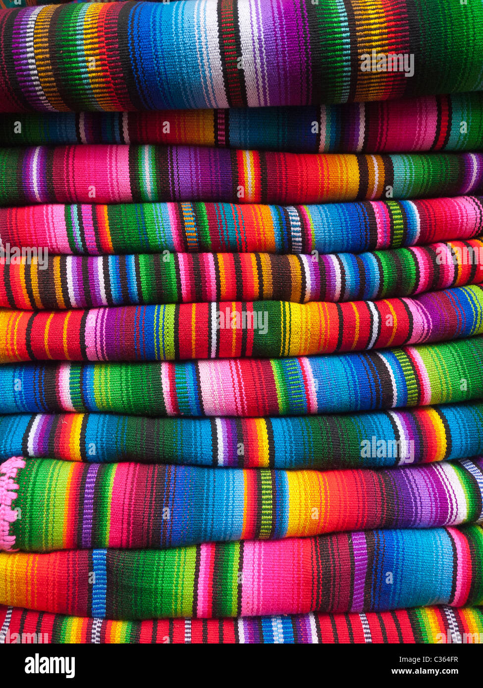 colorful blankets woven in a traditional manner are stacked up  - colorful blankets woven in a traditional manner are stacked up outside astore in chichicastenango guatemala
