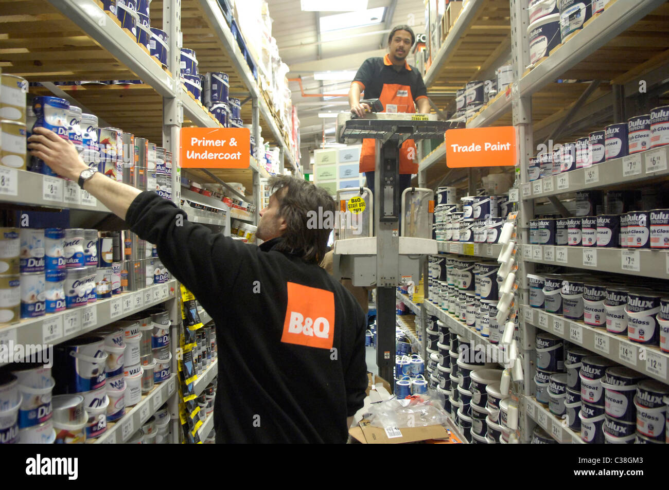 B&Q Employees Restocking Shelves In A Paint Isle Stock