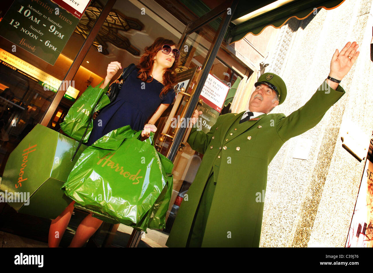 a harrods customer laden with her shopping is assisted by a famous stock photo royalty free. Black Bedroom Furniture Sets. Home Design Ideas