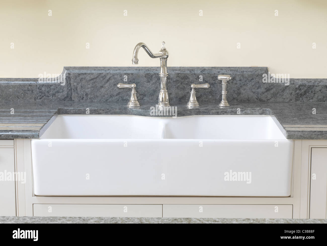 Double French Farmhouse Sink With The Ceramic Front Exposed And Set Under A  Granite Worktop With