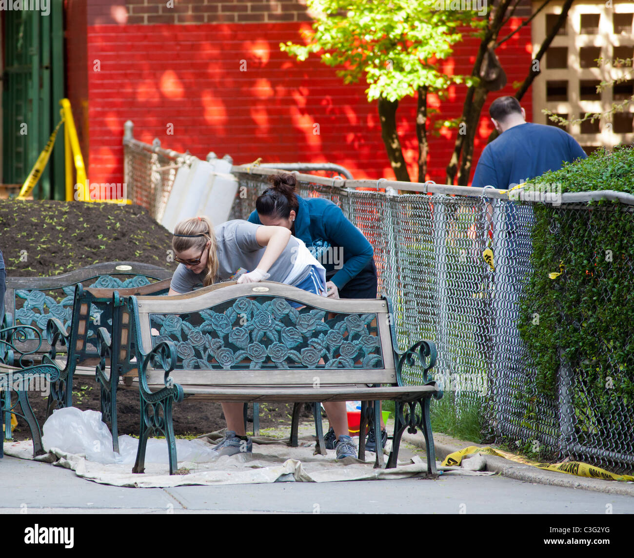 stock photo volunteers refinish garden furniture for a garden at a public school in new york