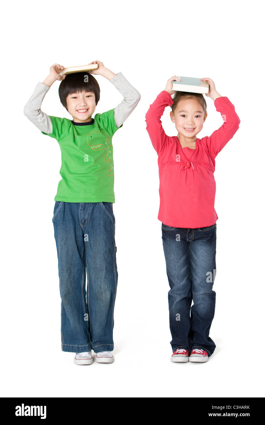two classmates holding books on their heads stock photo 36646391