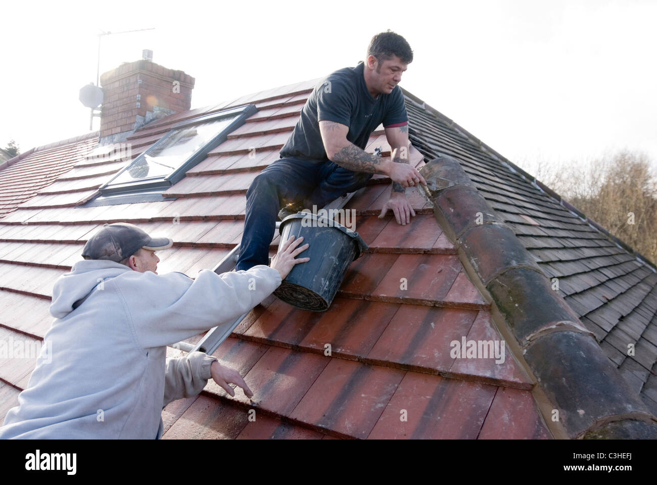 Roofer Laying Ridge Tiles With Mortar Completing Re