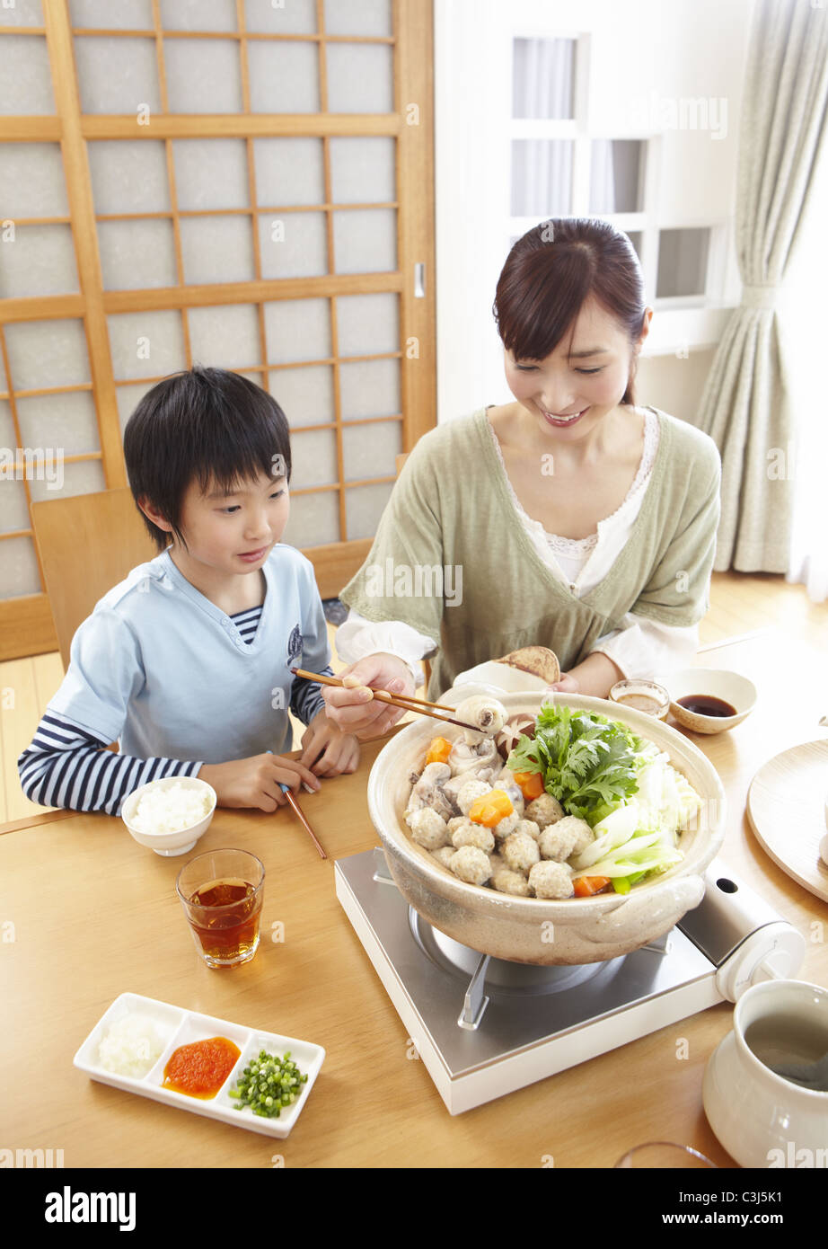 Mother And Son Sitting Around Japanese Hot Pot Stock Photo
