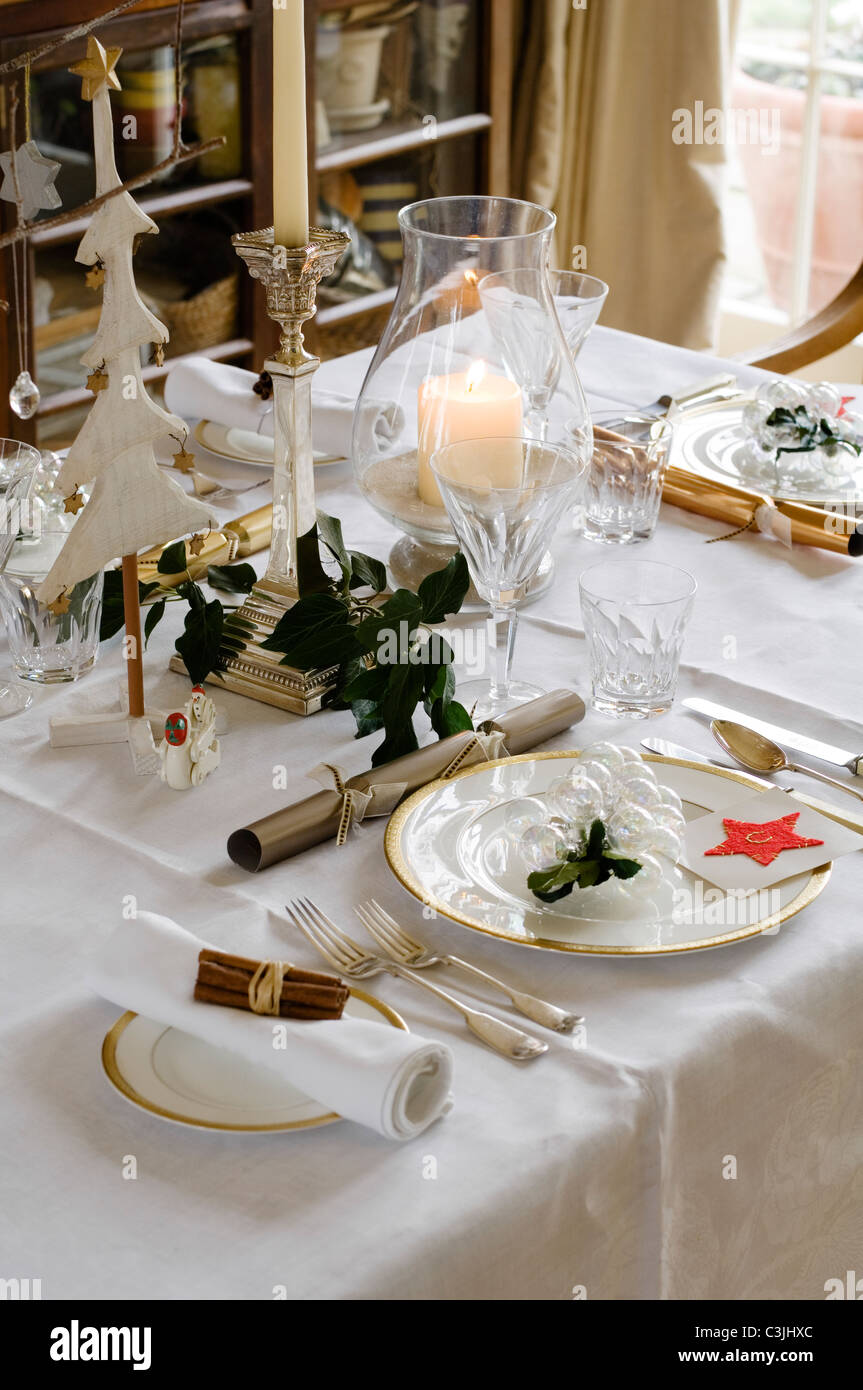 Festive table place setting with crackers, candles and glassware ...